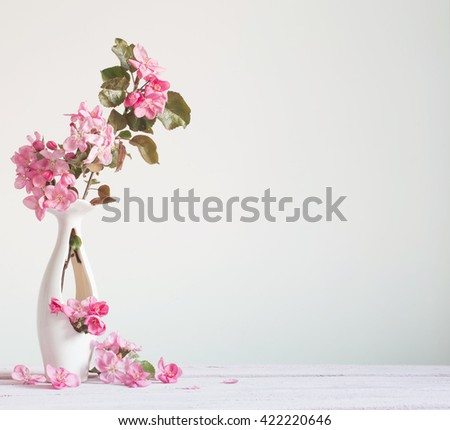 Beautiful ripe apples and branches in vase on white - stock photo