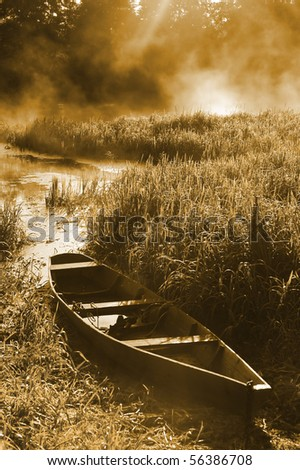 Beautiful river and old rowing boat in green grass - stock photo