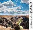Beautiful river in Charyn canyon and blue sky with clouds in Kazakhstan - stock photo