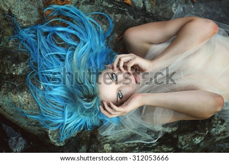 Beautiful river nymph posing on rocks. Fantasy and myth - stock photo