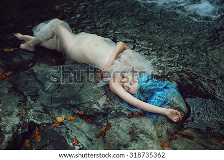 Beautiful river nymph sleeping on the stones . Fantasy and myth - stock photo