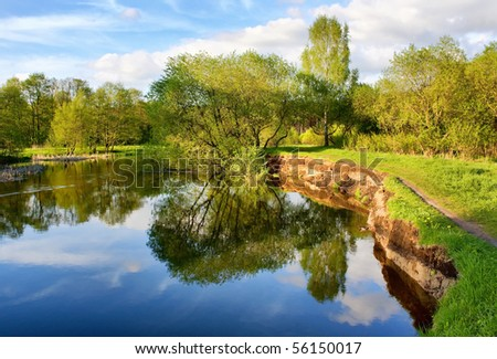 Beautiful riverside view with clouds and trees reflections - stock photo