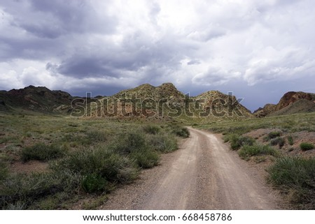Beautiful road in the steppe in a thunderstorm. Kazakhstan, canyon Charyn. In the spring. Epic landscape.
