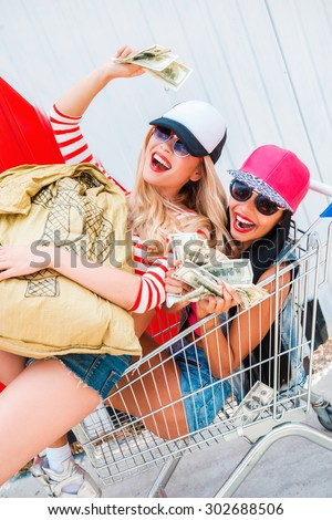 Beautiful robbers. Top view of two happy young women holding dollars and smiling while lying in shopping cart with money bag - stock photo