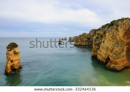 Beautiful rock formations, stone arches and caves at Dona Ana Beach and sailing boats on horizon (Lagos, Algarve coast, Portugal) in the evening light. - stock photo