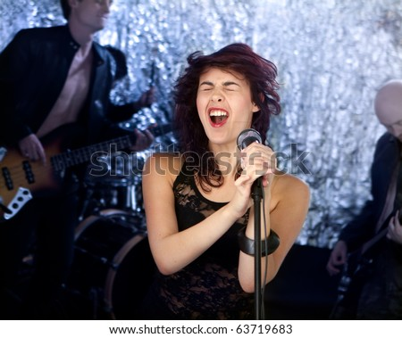 Beautiful rock singer with her band in the background - stock photo