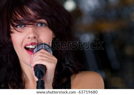 Beautiful rock singer with microphone - stock photo