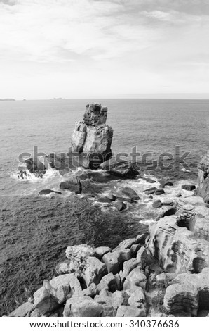 Beautiful rocks in water. Atlantic ocean coast near Peniche (Portugal). Aged photo. Black and white. - stock photo
