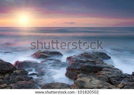 Beautiful rocky sea beach at the sunset