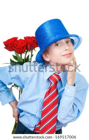 Beautiful romantic boy wearing a shirt, a tie and a blue hat holding red roses behind his back (Valentine gift concept)  - stock photo