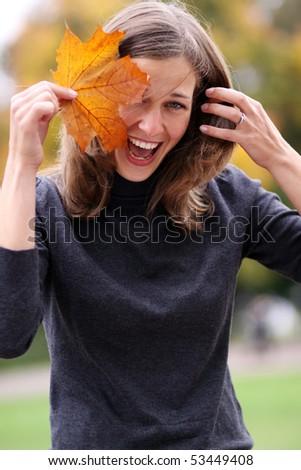 Beautiful romantic brunette with golden autumn leaf - stock photo