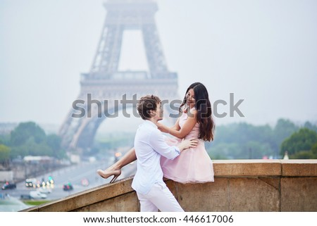 Beautiful romantic couple in love near the Eiffel tower in Paris on a cloudy and foggy rainy day