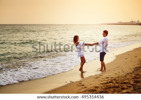 Beautiful romantic couple on the sea shore during sunset
