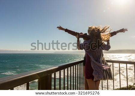 Beautiful Romantic couple tourist having fun laughing in funny titanic pose on terrace at sea. Happy man and woman holding together on travel vacation holidays on open ocean sea. - stock photo