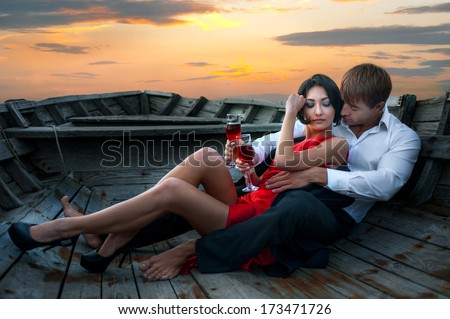 Beautiful romantic couple with wineglasses of red wine in old boat on sunset background - stock photo