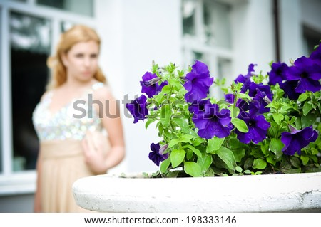 Beautiful romantic fashion girl in luxurious dress outdoors (focus on flowers) - stock photo