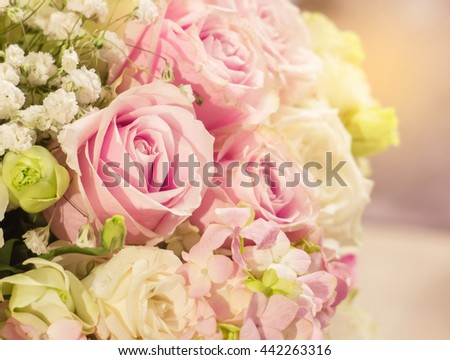 Beautiful Romantic Pink Rose Pattern in The Big Bouquet of Flowers Vase with Orange Sun Light Shade at The Corner for Interior Design, Selective Focus with Copy Space to input Text on Blur White Roses - stock photo