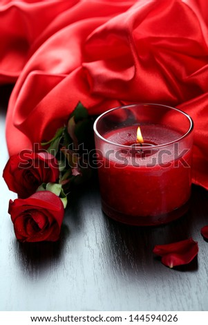 Beautiful romantic red candle with flowers and silk cloth, close up - stock photo