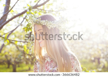 Beautiful romantic woman with long blond hair in a wreath of lily of the valley in the spring garden