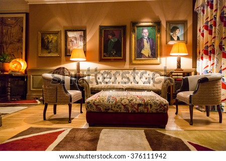Beautiful room with classical furniture, sofa, chairs paintings on the wall and decorations all around it in one of the London libraries.  - stock photo