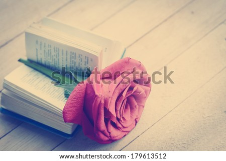 Beautiful rose and old book on wooden desk / Romantic nostalgic background - stock photo