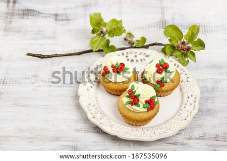Beautiful rose cupcake and blooming apple tree twig in the background - stock photo