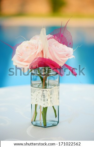 Beautiful roses bouquet in a jar with lace - stock photo