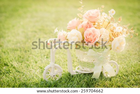 Beautiful roses flowers in a basket bicycle on green grass in the vintage retro style. (soft focus.)  - stock photo
