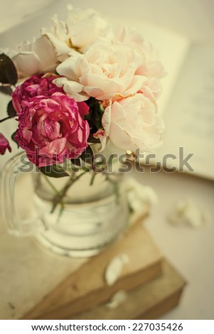 Beautiful Roses in a glass vase with books in vintage style