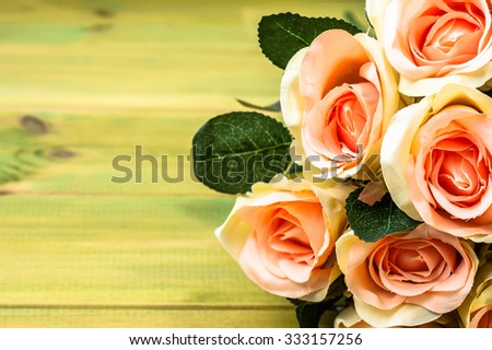 Beautiful roses on rustic wood background. Flowers backgrounds.