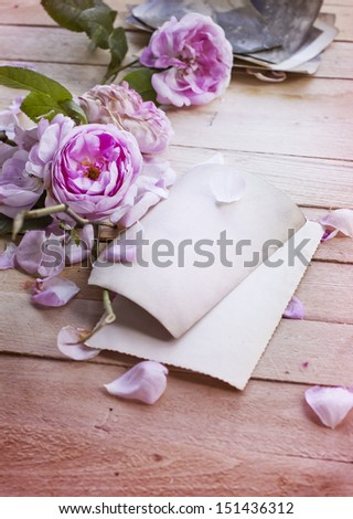 Beautiful roses with old paper card on wooden background/ holidays romantic background - stock photo
