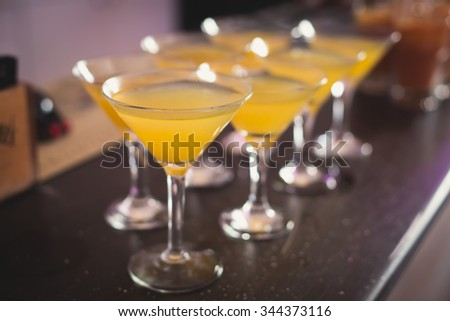 Beautiful row line of different colored alcohol cocktails with mint on a christmas party, martini, vodka with bubbles,and others on decorated catering bouquet table on open air event, picture