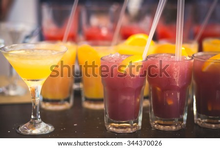 Beautiful row line of different colored alcohol cocktails with mint on a party, martini, vodka with bubbles,and others on decorated catering bouquet table on open air event, picture with bartender