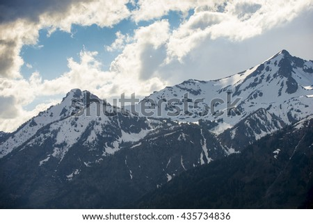 Beautiful rugged rocky Teton snow capped mountain range blue sky majestic landscape scene with dramatic clouds - stock photo