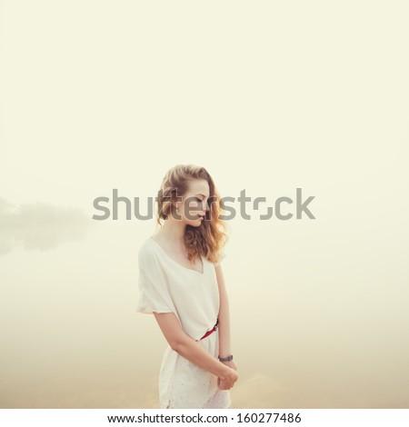 beautiful sad girl in the morning on the beach - stock photo
