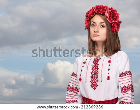 Beautiful sad girl in the Ukrainian national suit against the cloudy sky - stock photo