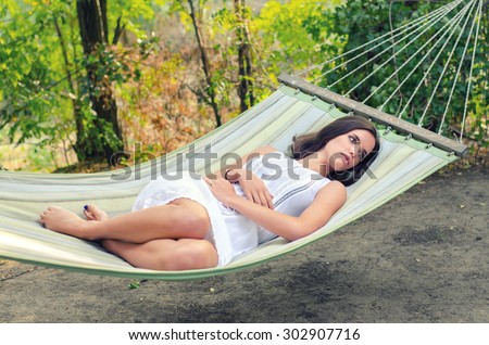Beautiful sad girl in white dress lying in hammock in summer forest. - stock photo