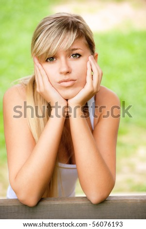 Beautiful sad girl sits on bench against summer nature.