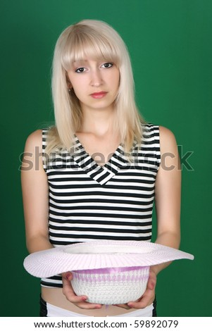 Beautiful sad girl with hat in hand - stock photo