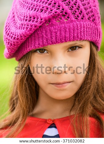 Beautiful sad little girl in red beret closeup on background of city park.