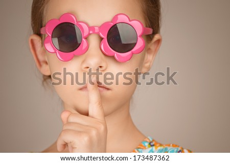 Beautiful sad little girl puts index finger to lips, on brown background. - stock photo