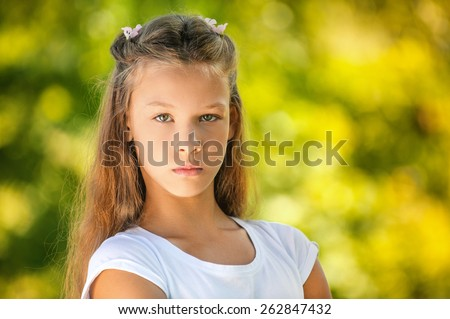 Beautiful sad teenage girl in white blouse, against green of summer park. - stock photo