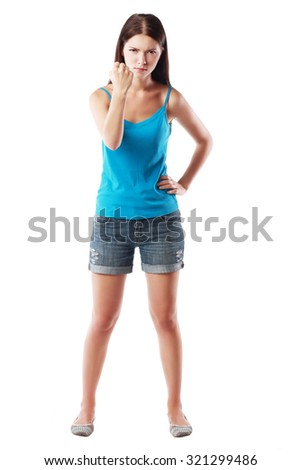 Beautiful sad young woman close-up threatens fist into camera, isolated on white background full body