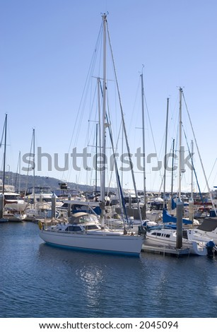 beautiful sailboat sits in the water in a harbor - stock photo