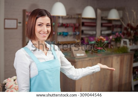 Beautiful saleswoman is raising her left hand sideways and showing her flower shop proudly. The woman is smiling and looking forward with joy