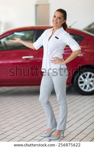 beautiful saleswoman presenting new car to clients - stock photo