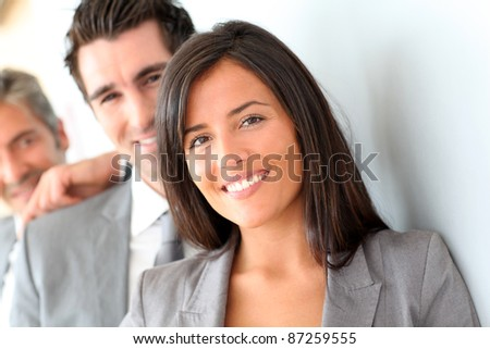 Beautiful saleswoman standing with group of business people - stock photo