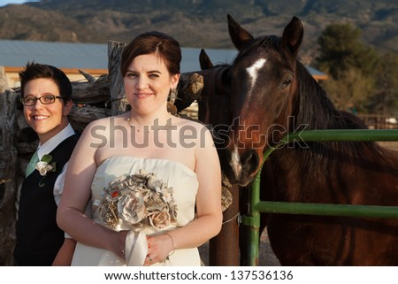 Beautiful same sex couple near horse at ranch