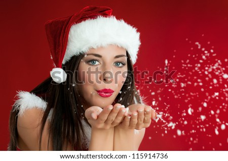 Beautiful santa claus girl blowing white snowflakes from her hands on red christmas background - stock photo