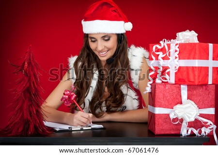 beautiful santas helper with headset taking notes - stock photo